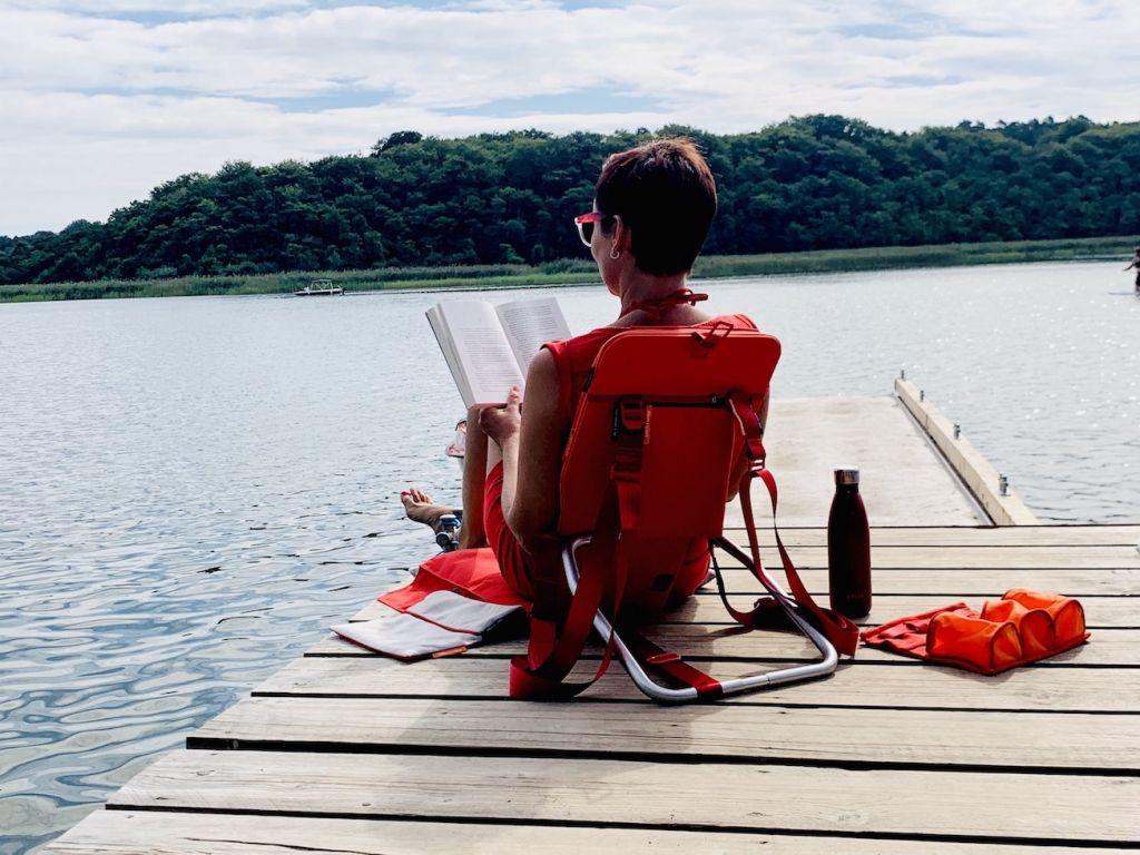 Frau entspannt Buch lesend mit Rückenlehne am See