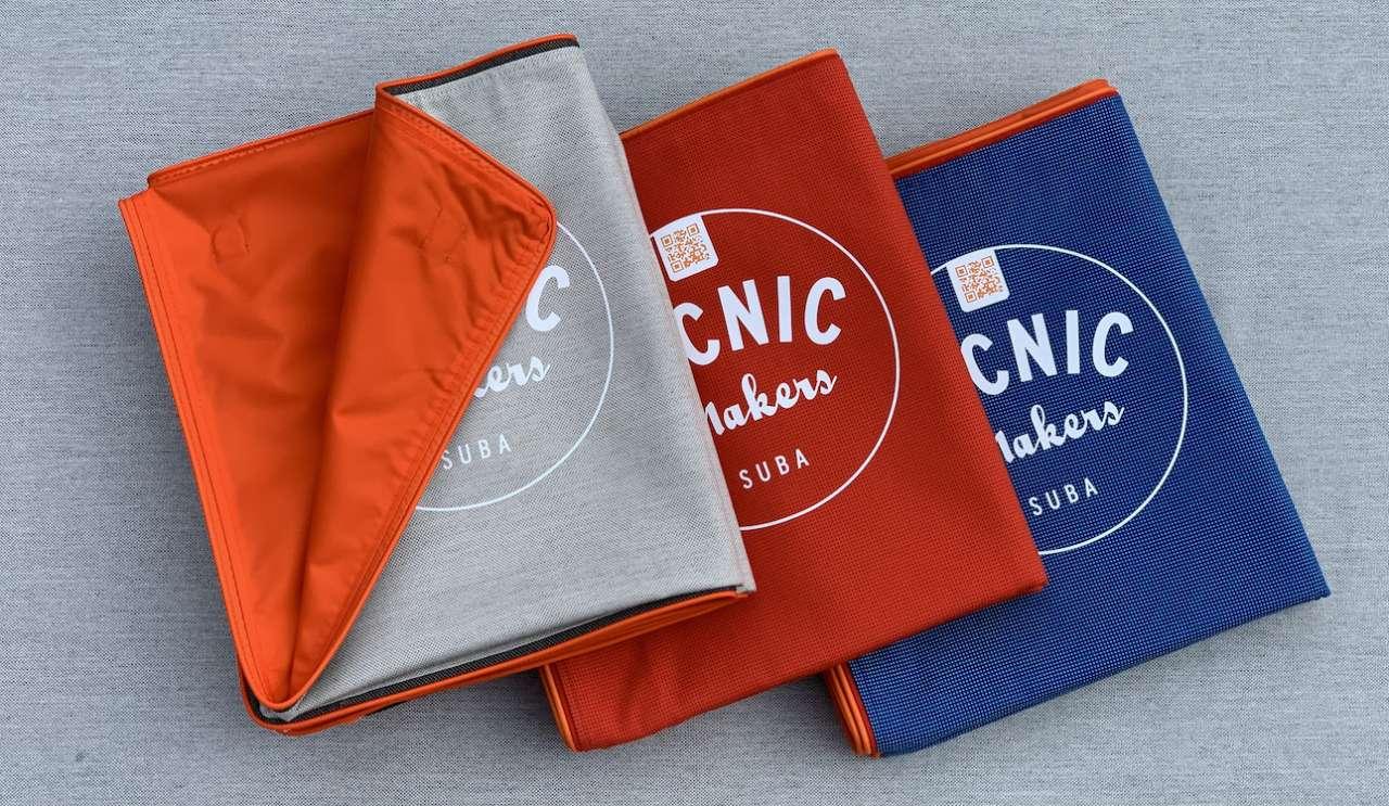 Picknickdecken suba.squarepark gefaltet mit Logo in .red, .ocean und .silvergrey