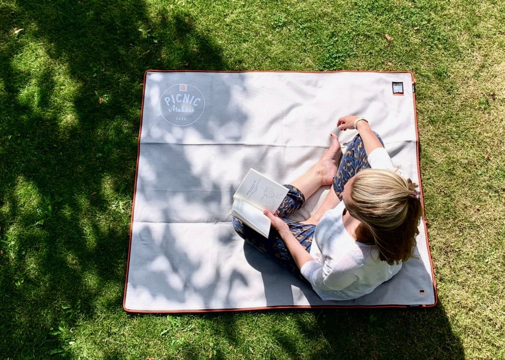 Auf Picknickdecke im Park ein Buch lesen